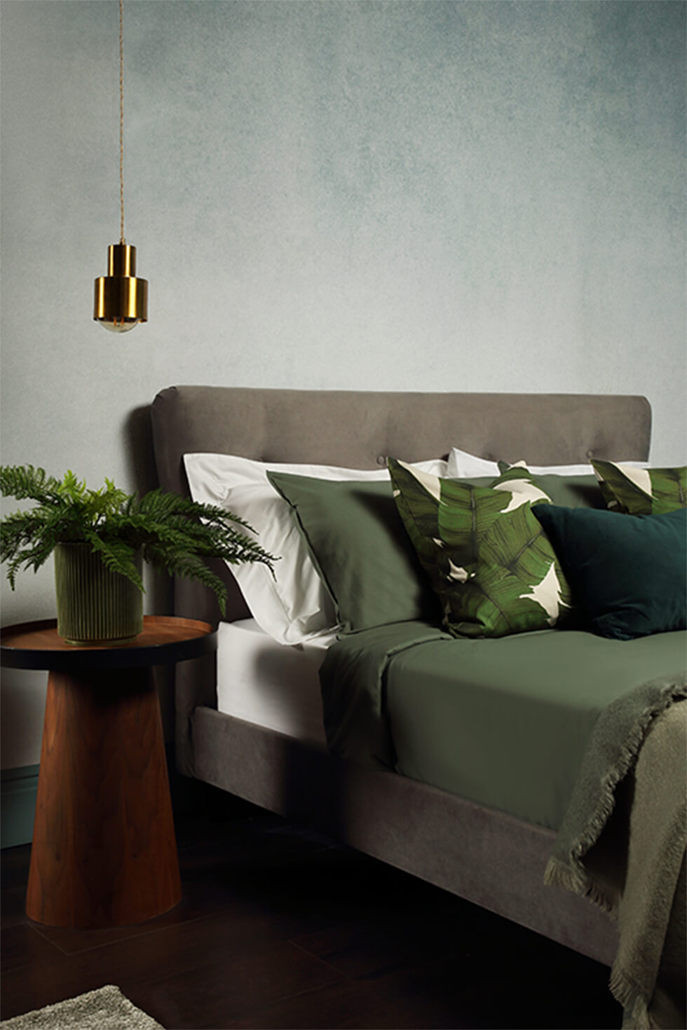 Relaxing green bedroom with grey bed, indoor plants and gold lamp