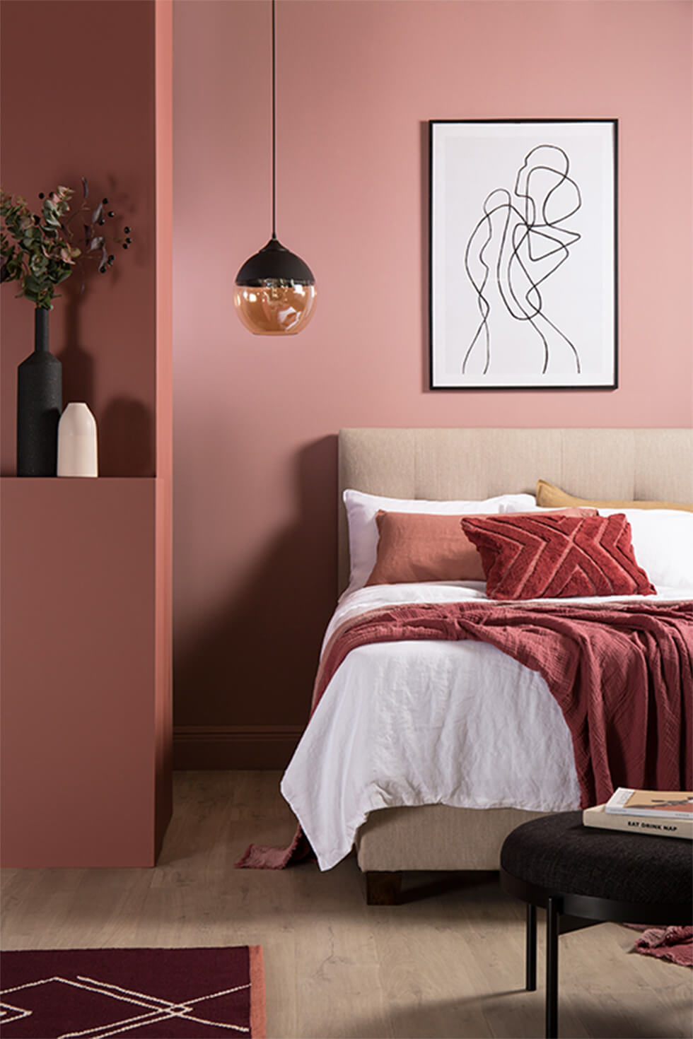 Pink bedroom with fabric bed, glass pendant lamp and terracotta accents