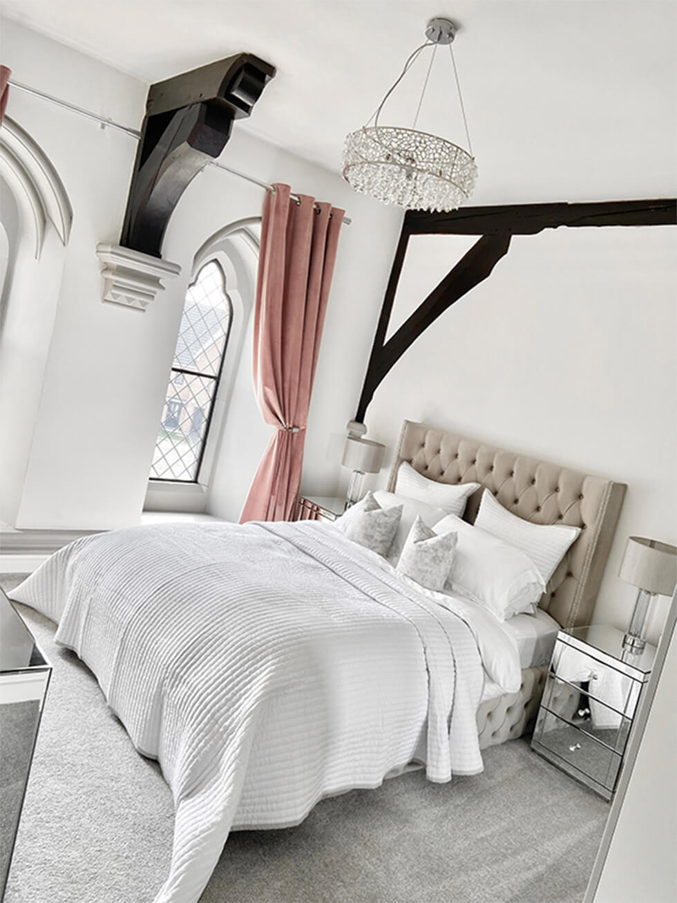 grey bedroom with cosy bedding and luxurious chandelier
