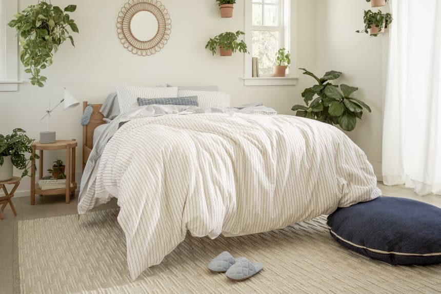 Cosy bedroom with striped bedding and indoor plants