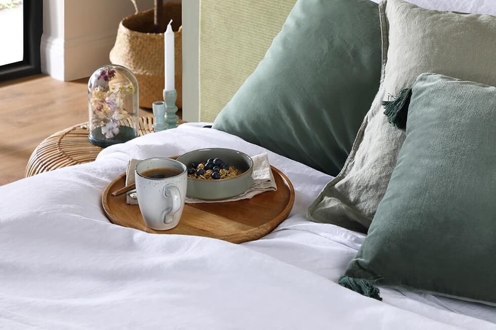 Close up of a bed with sage green and grey pillows and rattan side table