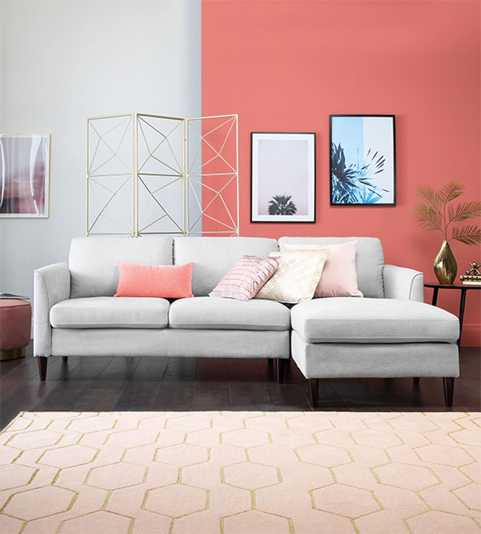 Grey corner sofa against a bright coral and grey feature wall.