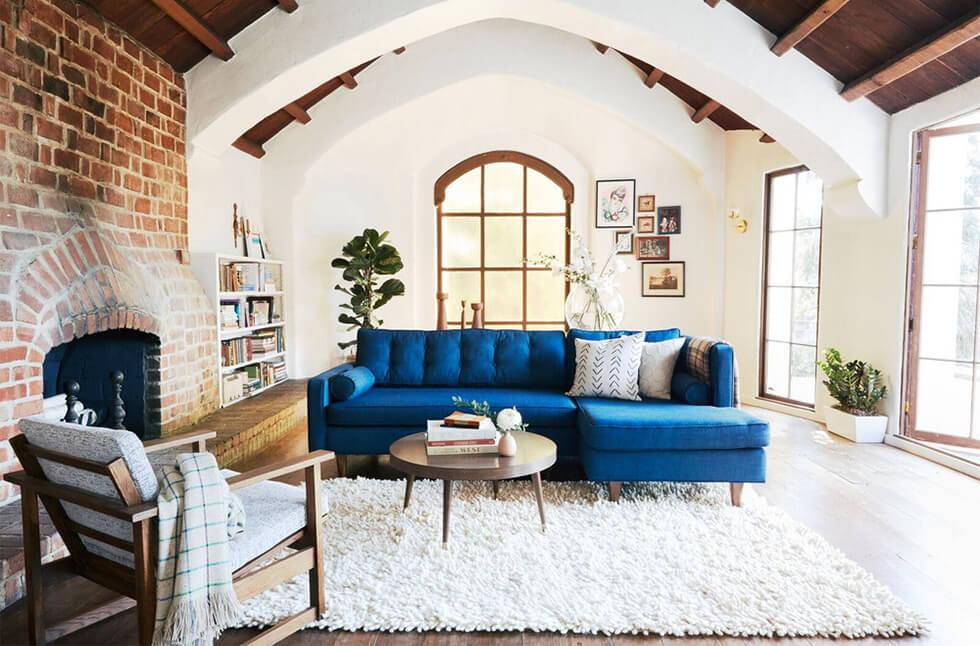 A blue corner sofa with a furry rug in a rustic style living room.