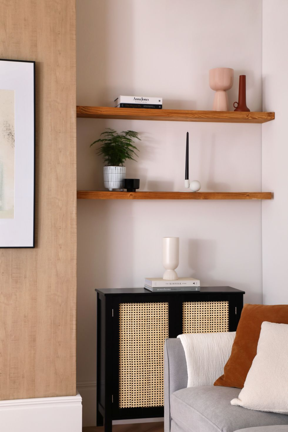 Modern living room with potted plant, vases, books and candle on the wooden shelf