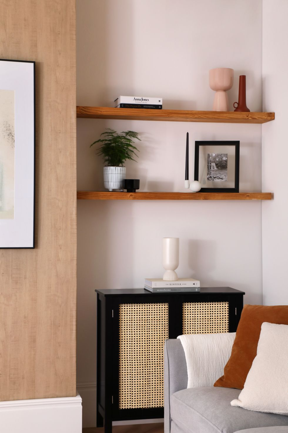 Modern living room with potted plant, vases, books, candle and framed photo on the wooden shelf