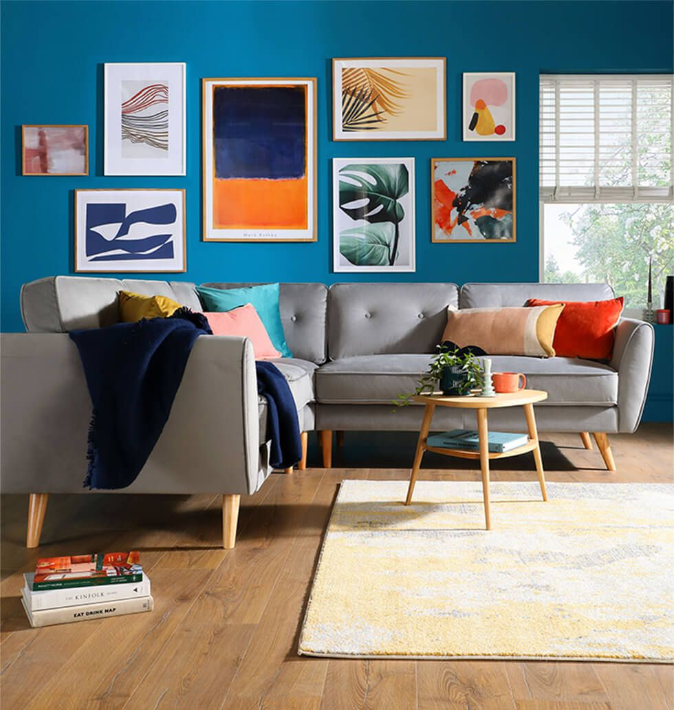 Modern velvet sofa in a living room with a colourful feature wall