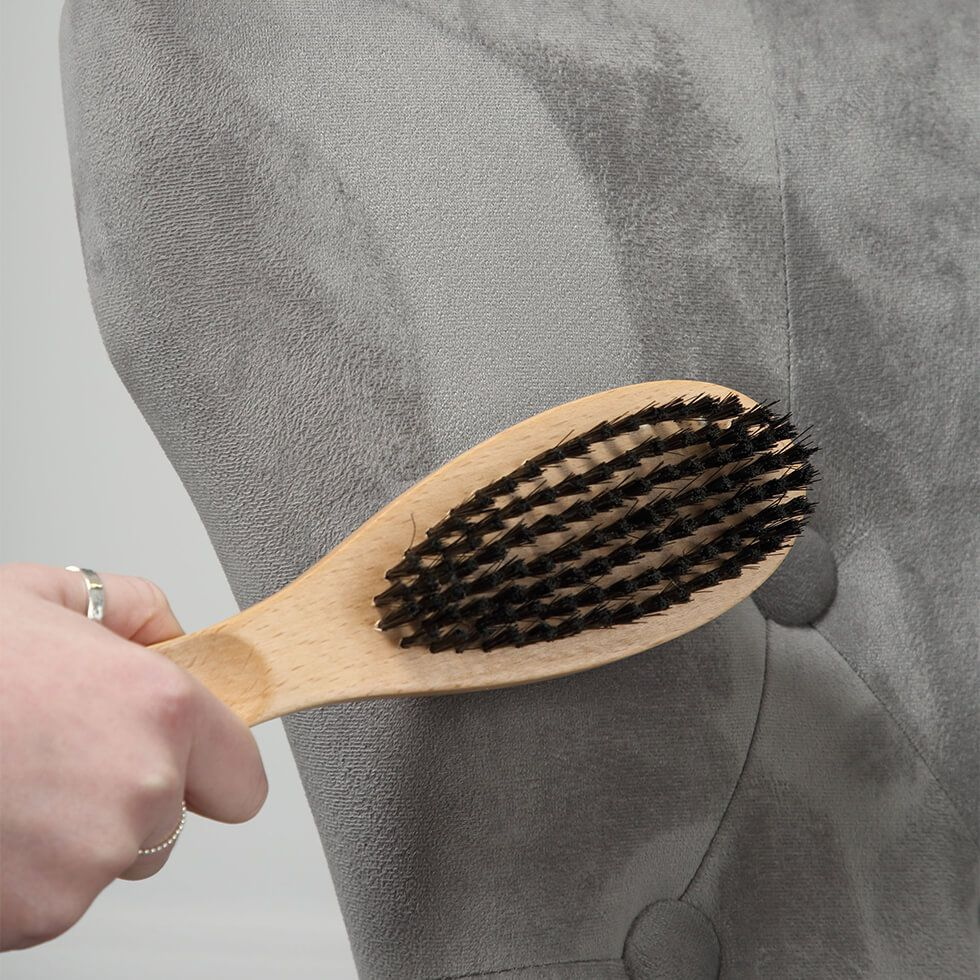 Brushing the sofa with the flat side of the brush