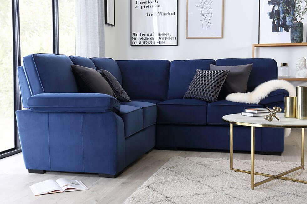 Classic blue velvet sofa in the living room with a minimalist brass coffee table