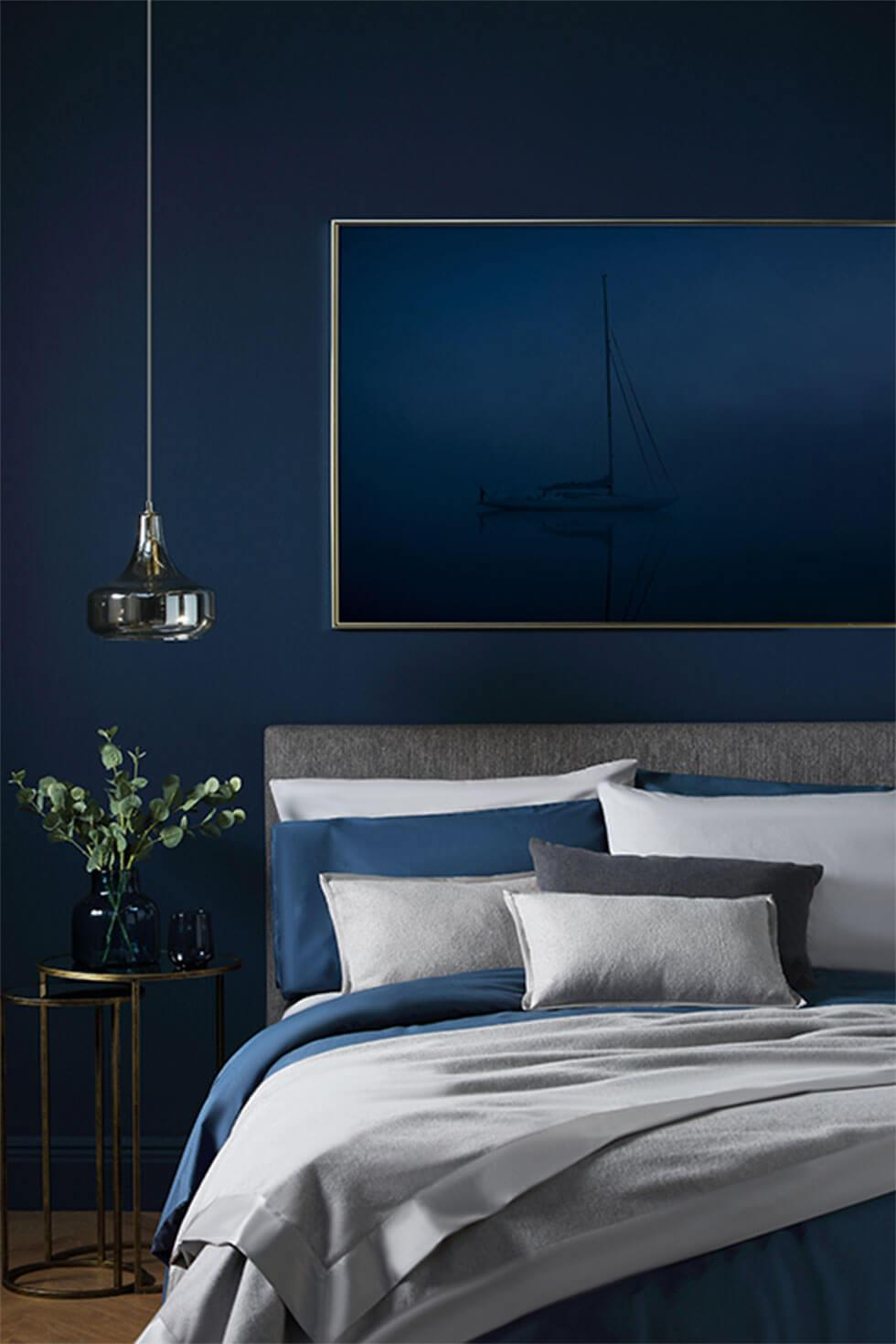 Classic blue bedroom with feature wall and cosy bedding
