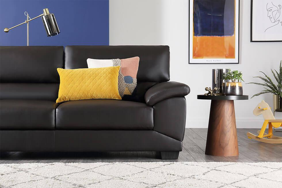Black leather sofa in a colourful living room with a classic blue wall