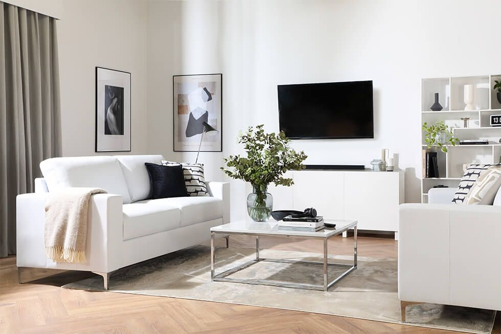 Dramatic monochrome living room with white leather sofa and dark walls