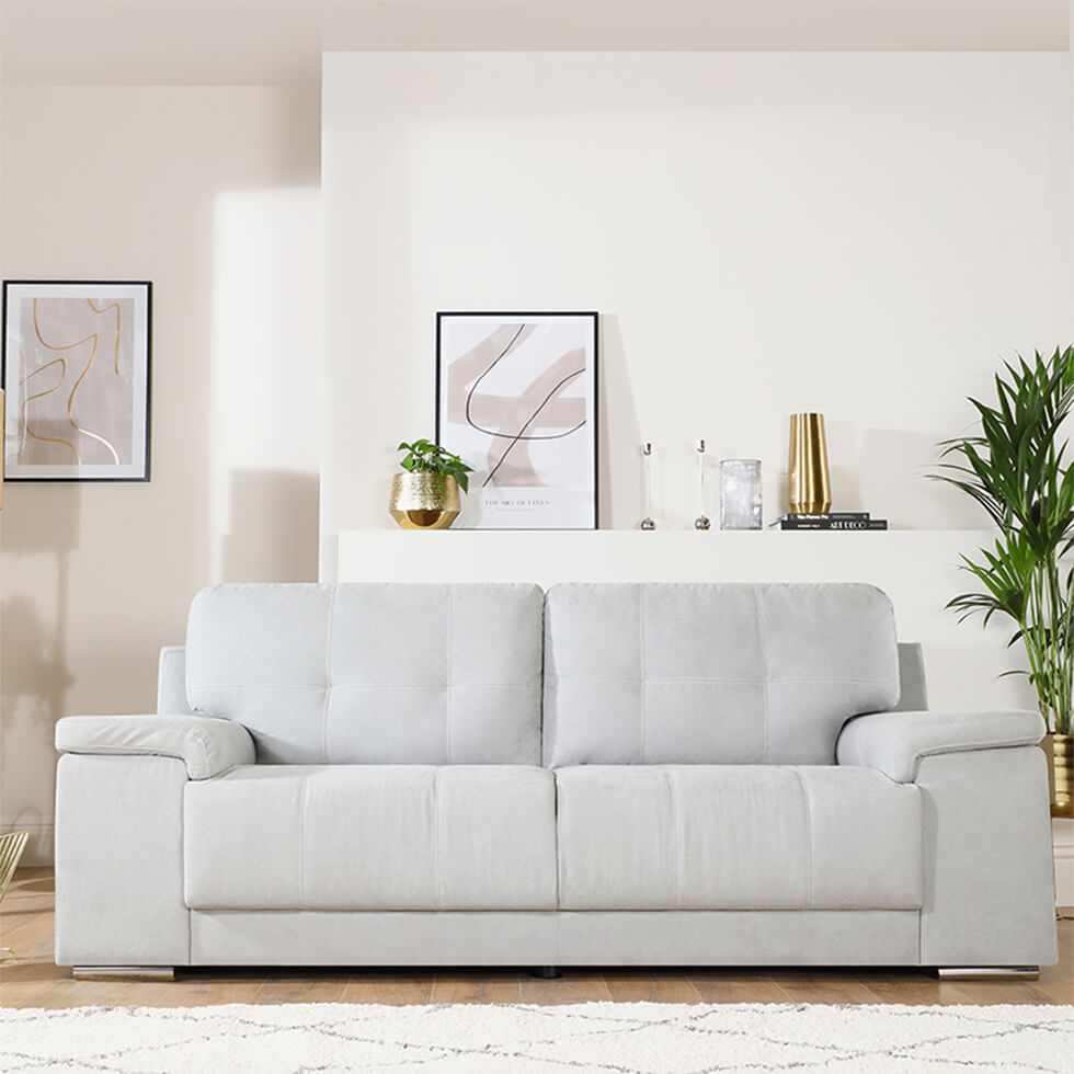 cosy neutral living room with light grey fabric sofa, rug and indoor plants