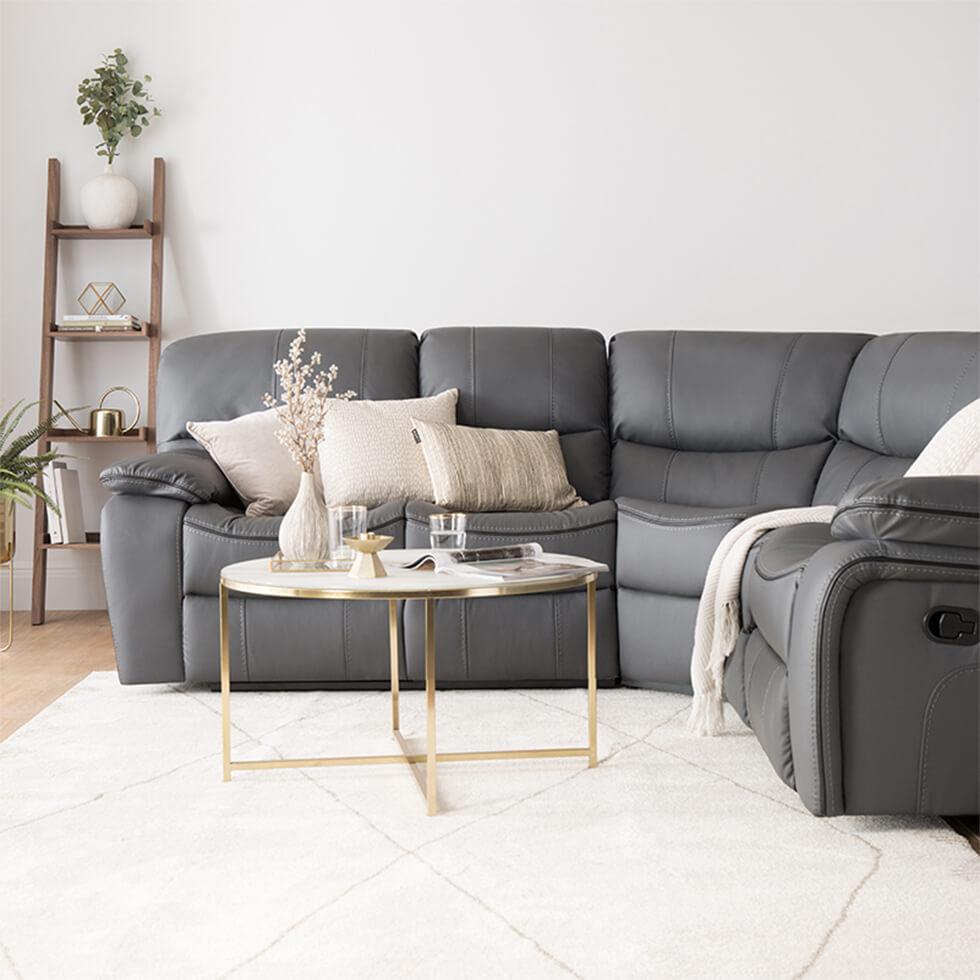 dark grey corner sofa with modern gold coffee table