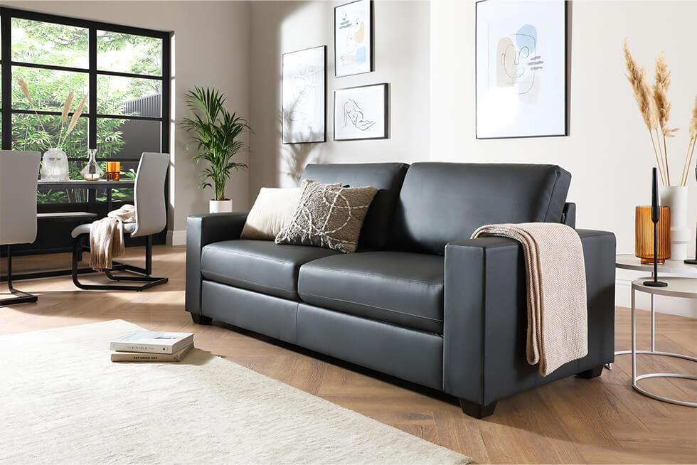 Grey leather sofa with a cosy throw and pillows