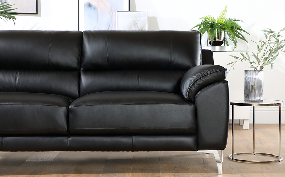 Black leather sofa with chrome legs in a modern living room