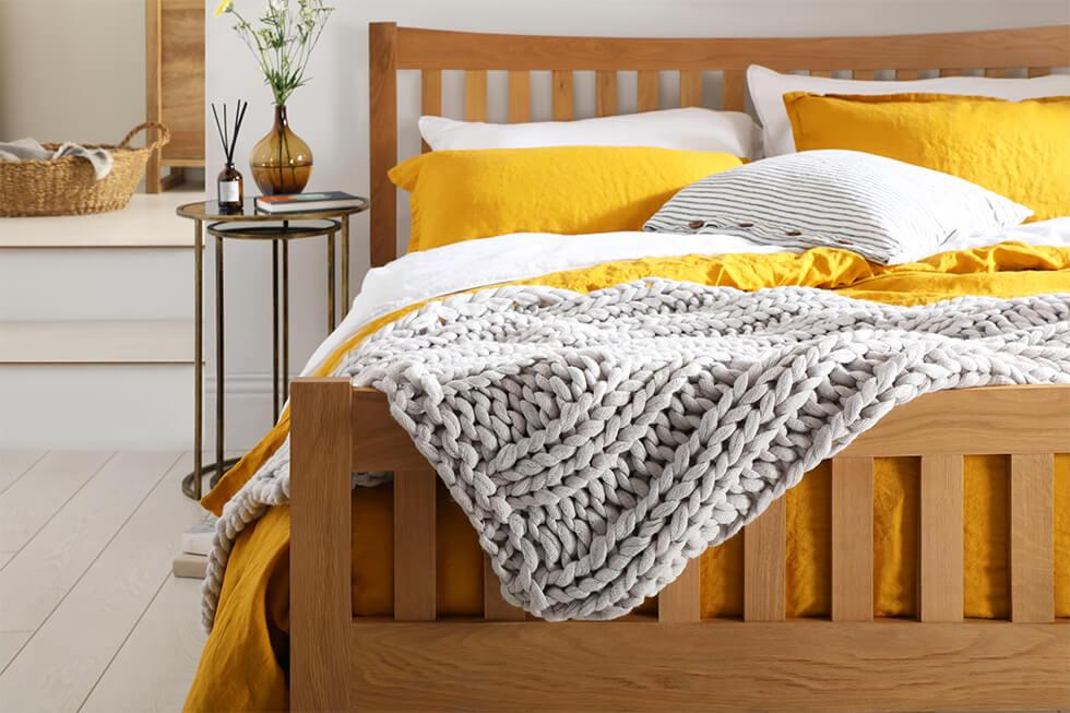 Coastal bedroom with oak bed, yellow bedding and grey knit throw