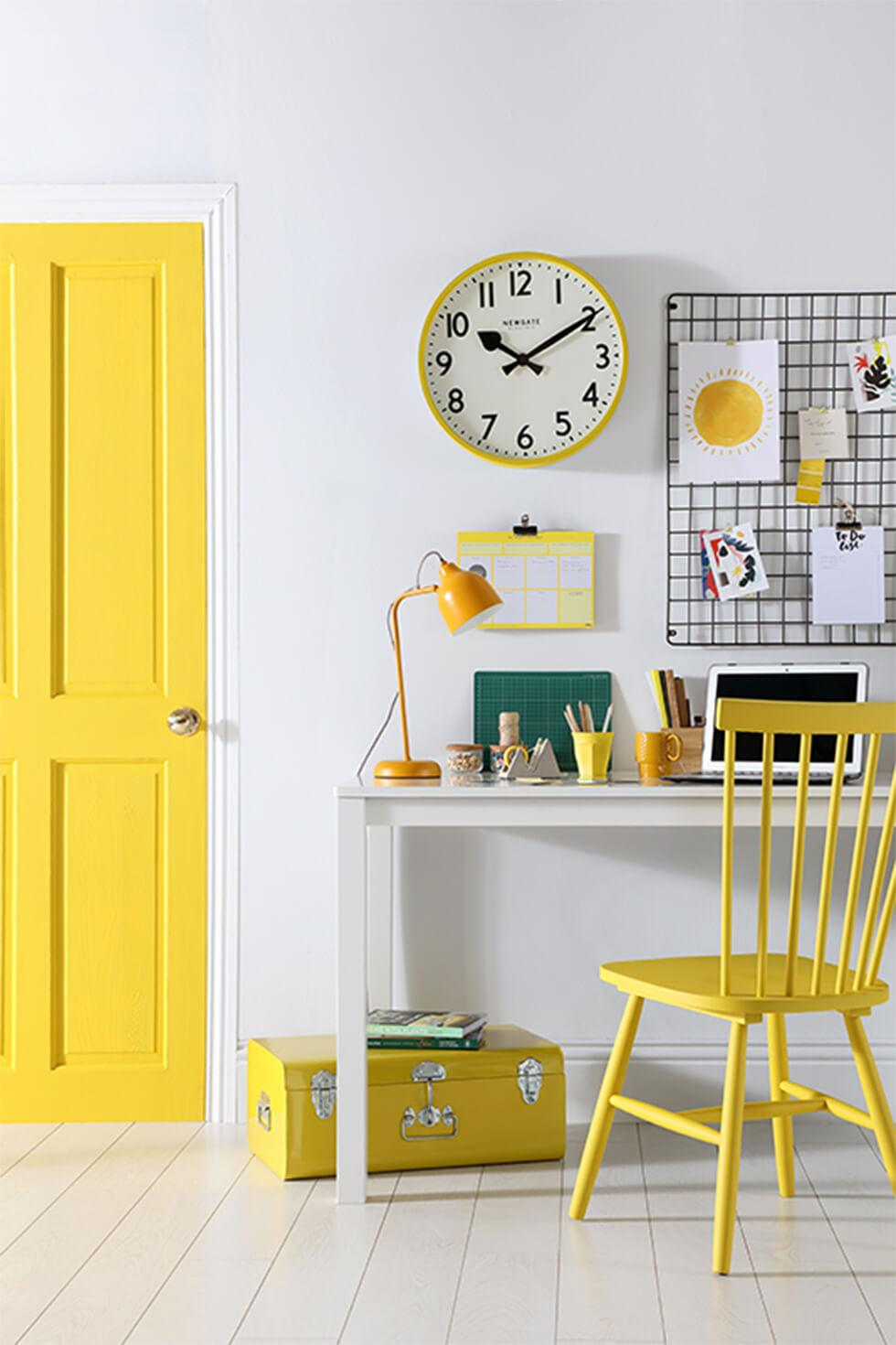 Bright home office with white table and yellow chair