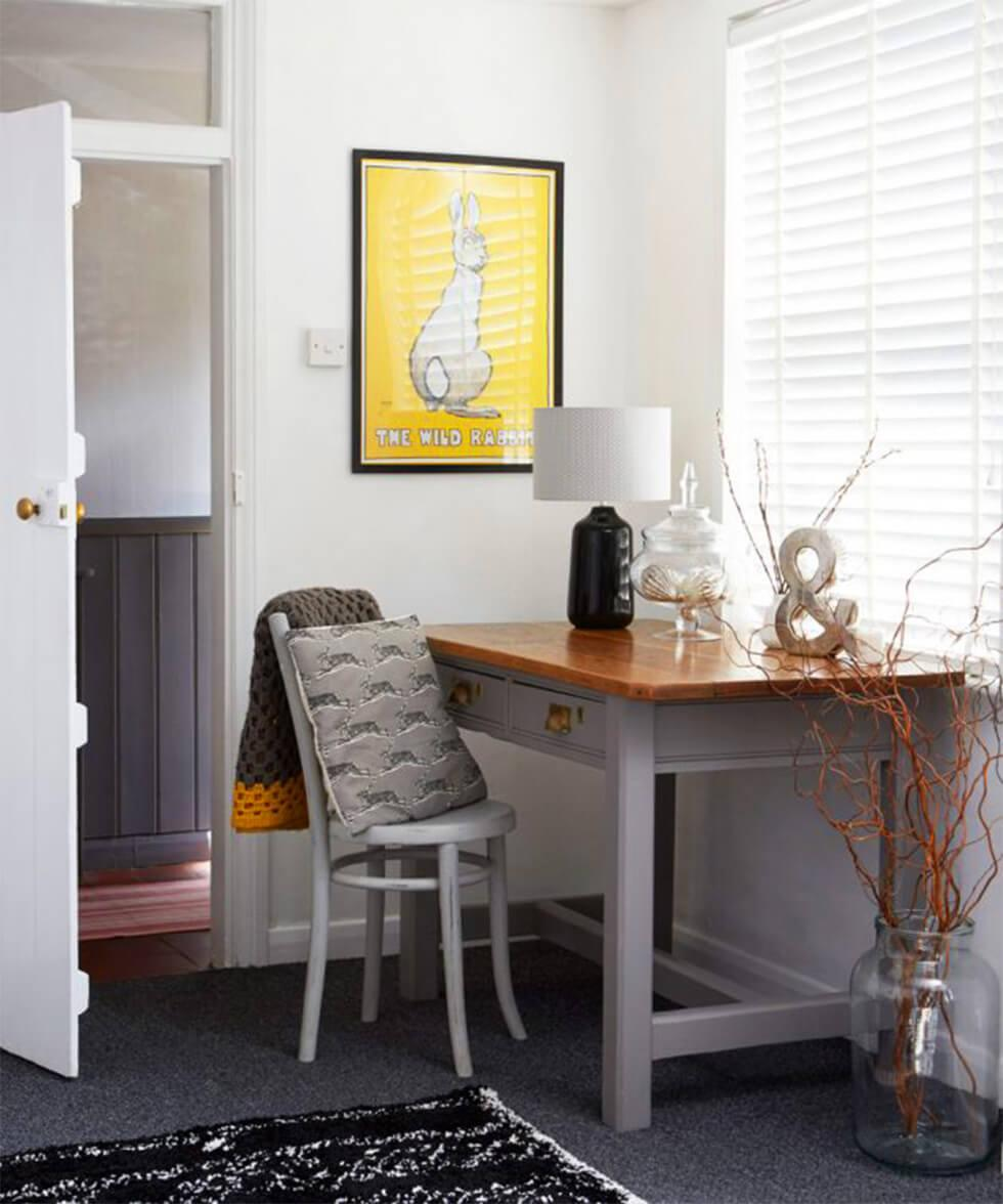 Grey and yellow home office with framed art