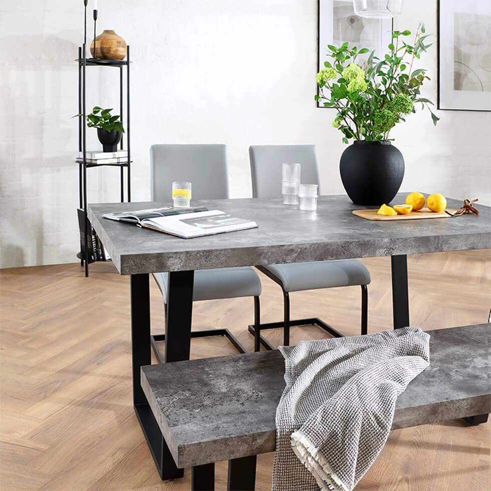 Industrial dining space with concrete table and bench and grey leather chairs