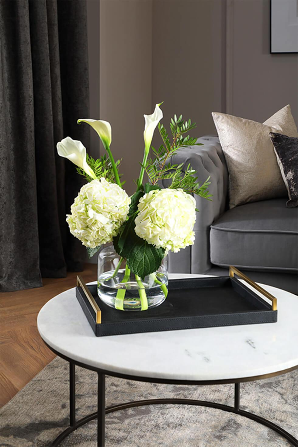 Marble coffee table with dark tray, and a vase of flowers