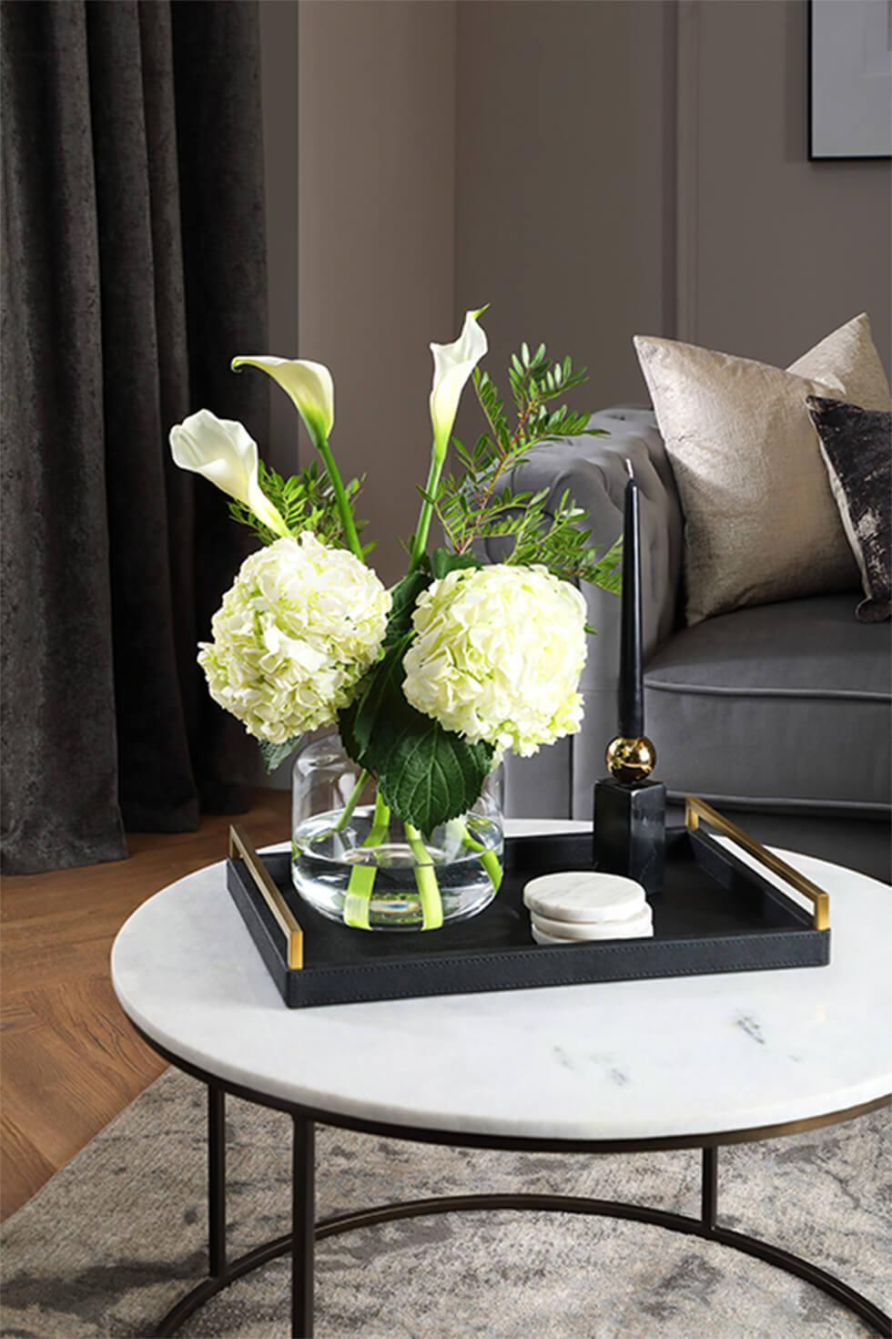 Marble coffee table with dark tray, vase of flowers, candle and marble coasters