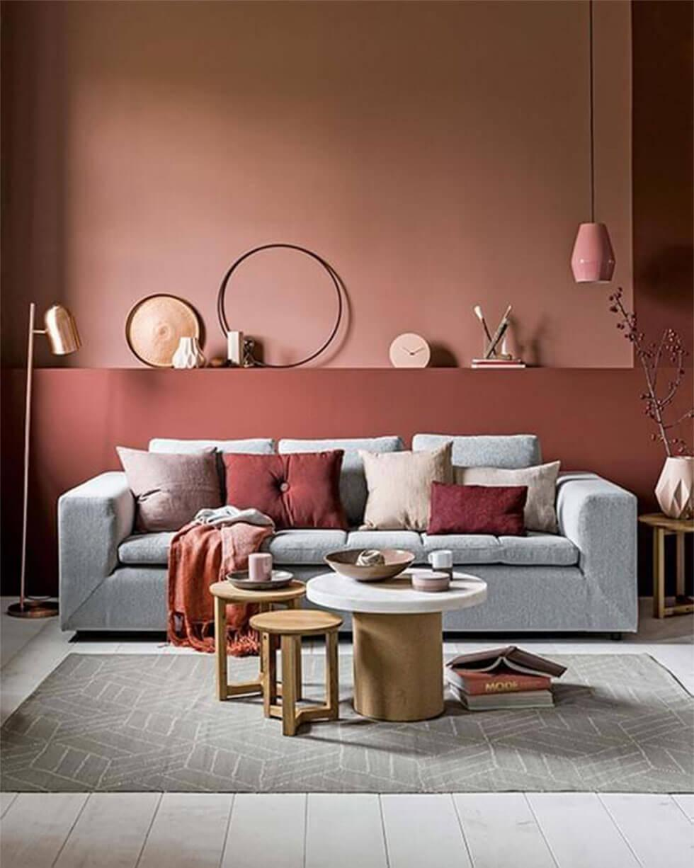 A grey sofa in a Scandinavian style living room with terracotta and burgundy walls.