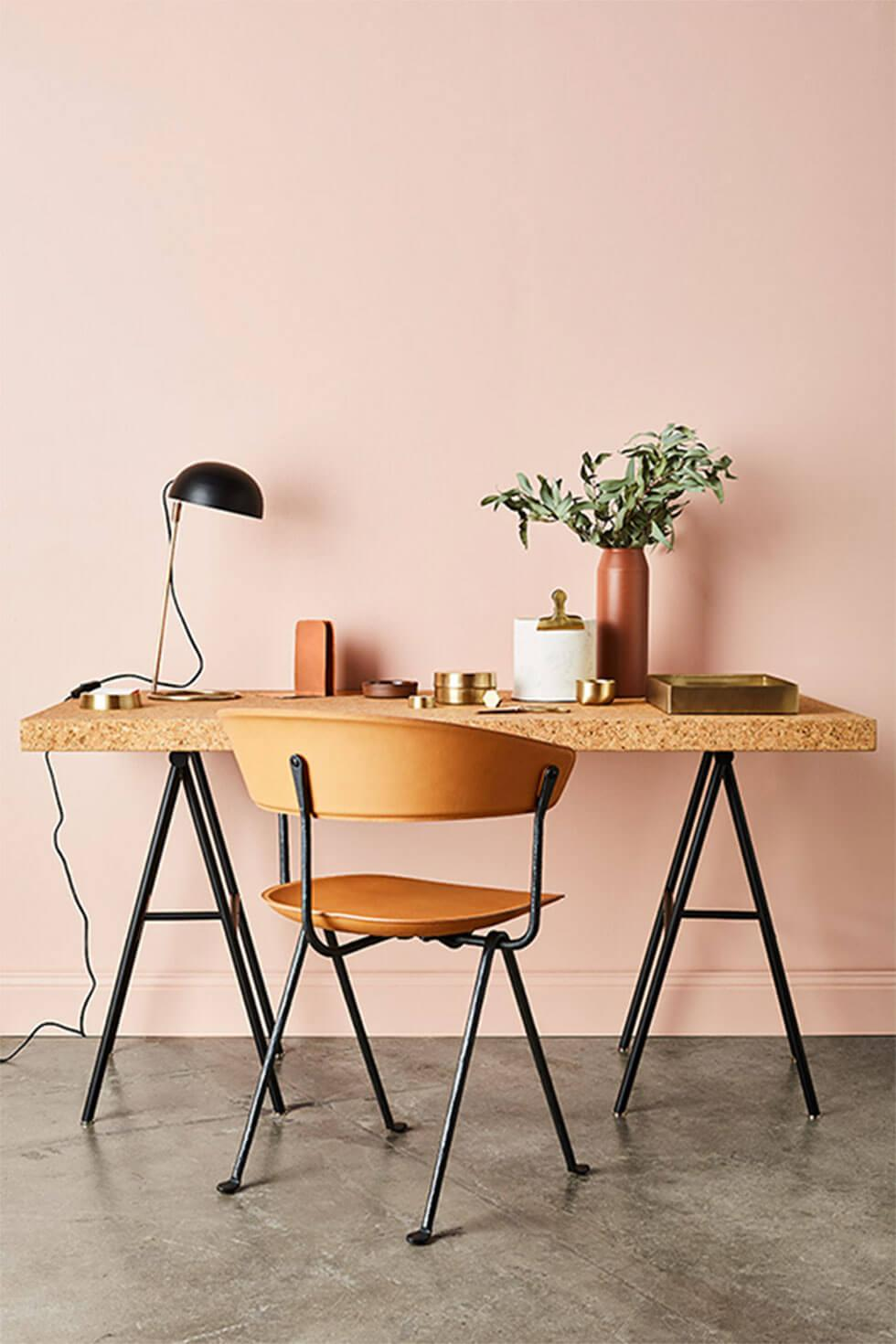 Nordic design inspired home office with dusty pink walls, wooden chair and desk with brass accents.