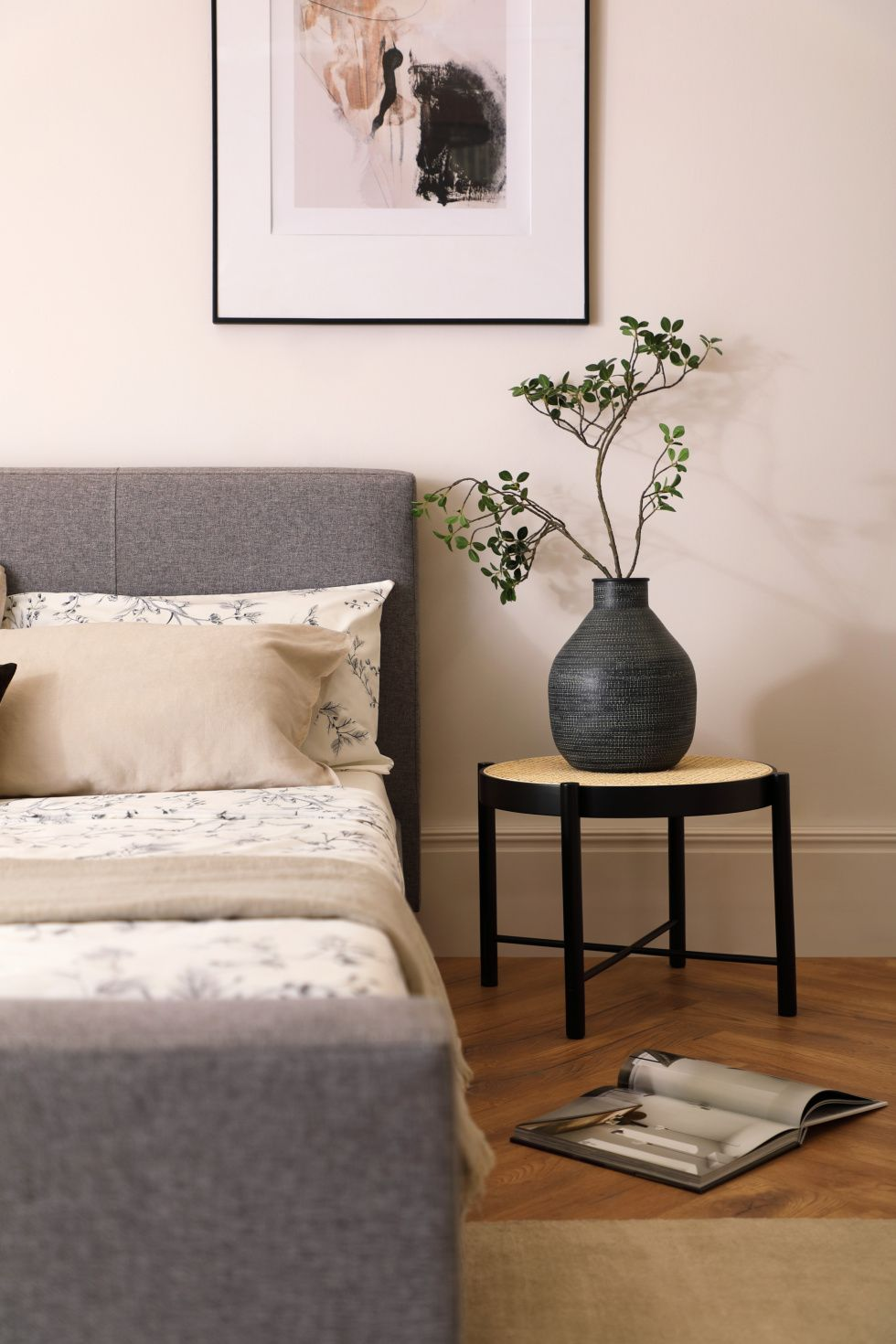 Grey fabric bed and potted plant in a Japandi bedroom