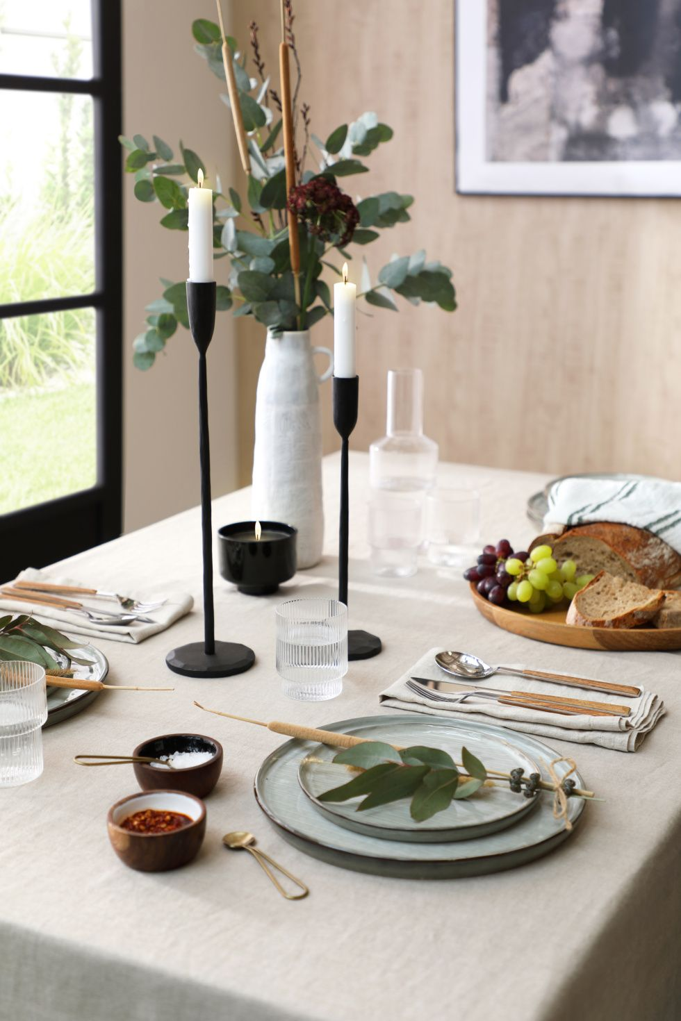 Japandi style dining table with ceramic dinnerware and a plant centrepiece