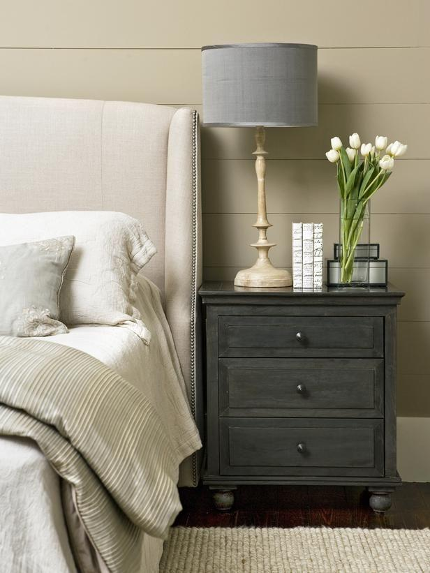 Dark grey side table with grey lamp and white flowers.