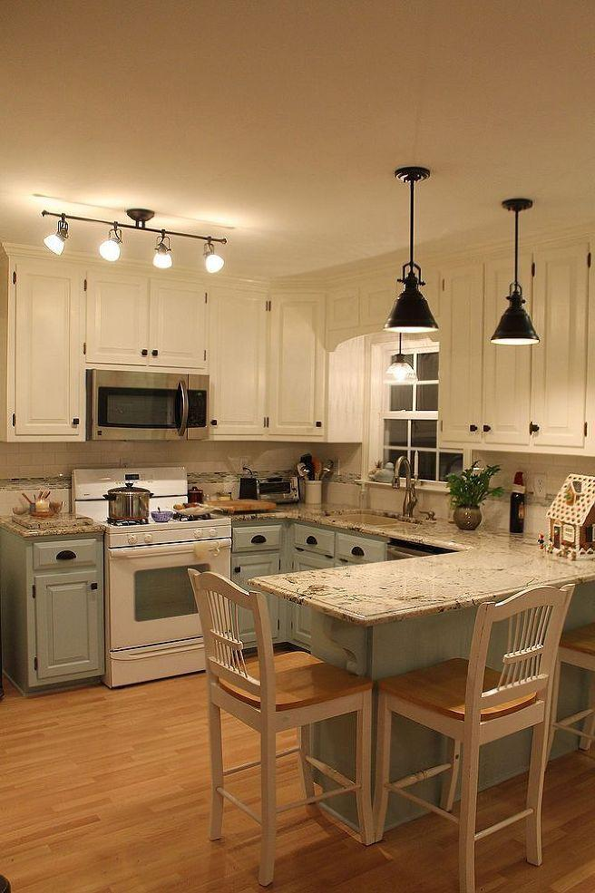 Marble topped kitchen counter with blue-grey cabinets and wooden floor
