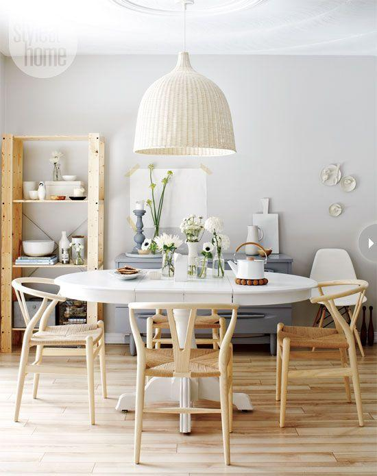Airy and white dining room with white table, wooden floors and chairs, and white lamp.
