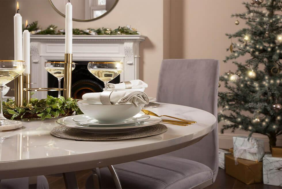 White marble dining table decorated in a glamorous Christmas dinner setting.
