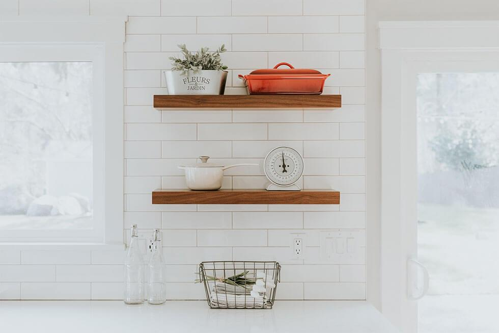 Wooden kitchen shelves with Le Creuset cookware.