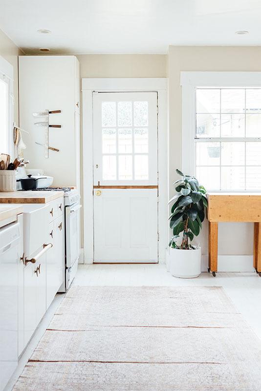 Tidy white kitchen interior with indoor plants