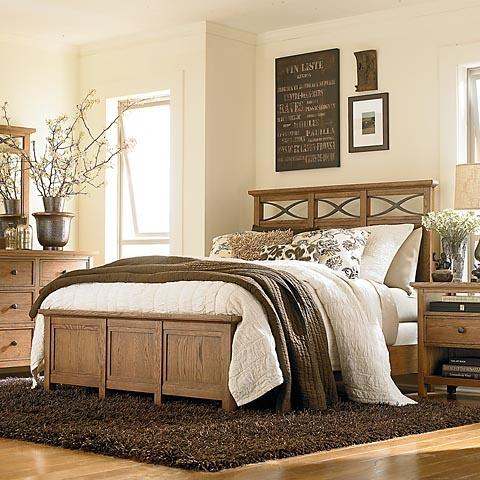 Country bedroom with wooden bed and white flowers.