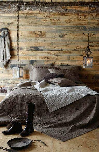Bedroom with wooden walls and floors, and grey bedding