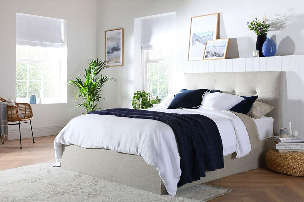 Oatmeal fabric bed in a modern coastal bedroom