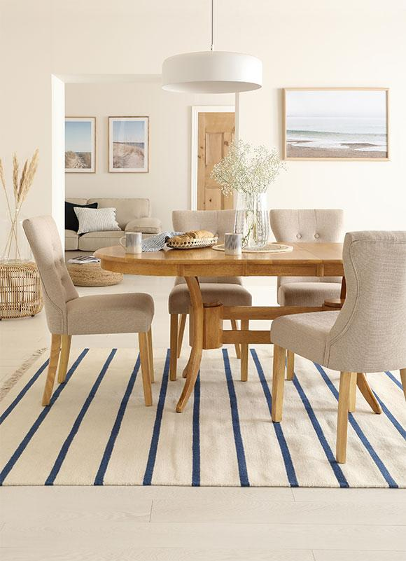 oak dining set with fabric dining chairs and striped rug