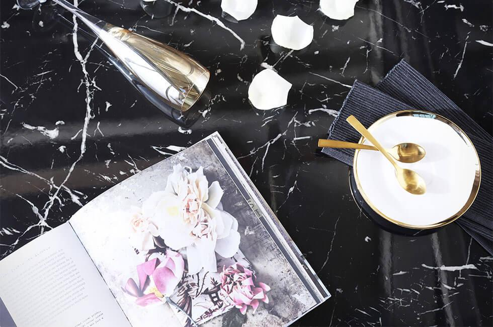 Flat lay of a marble dining table top with a magazine, and gold cutlery.