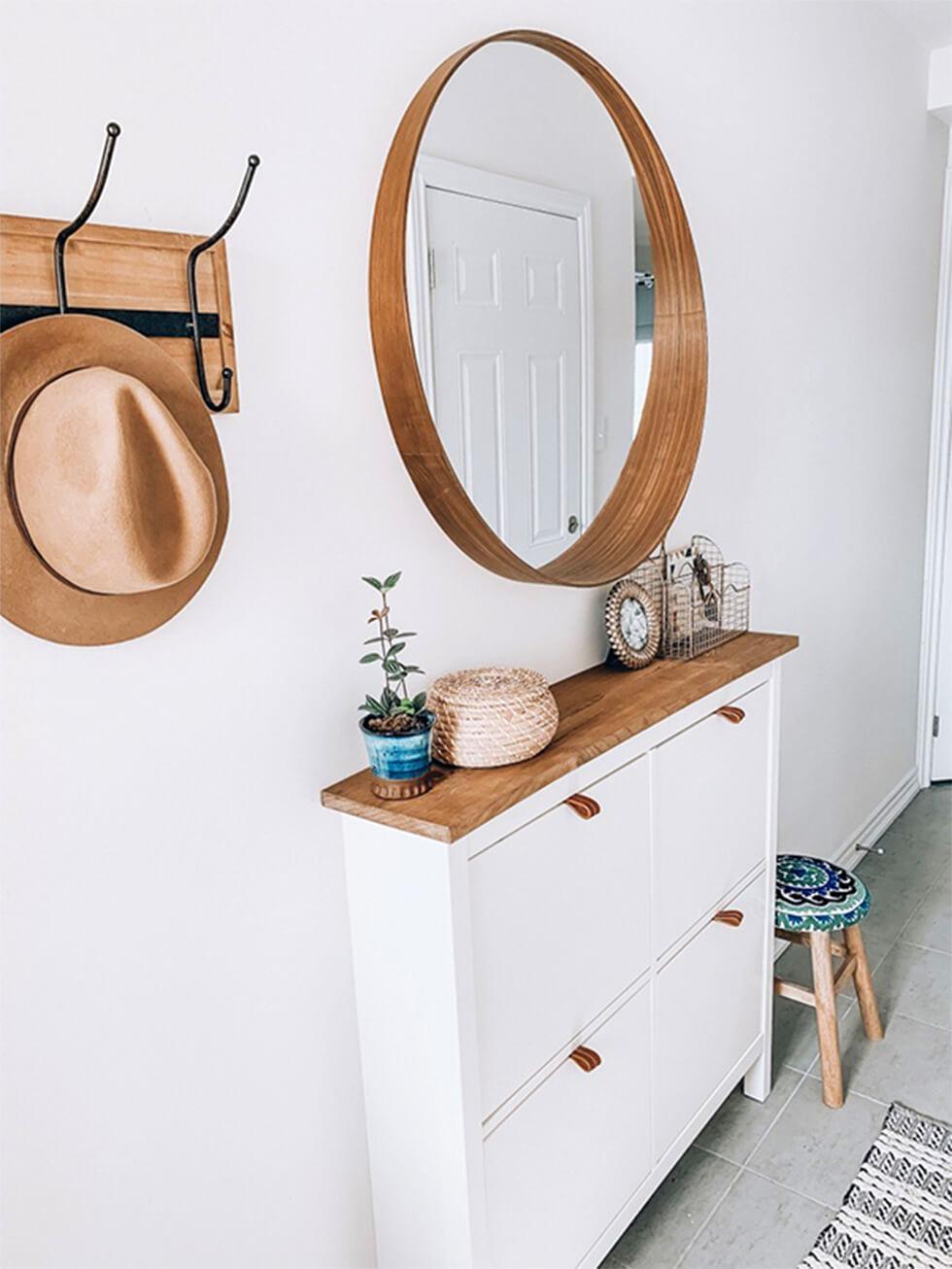 White hallway with storage closet and round mirror