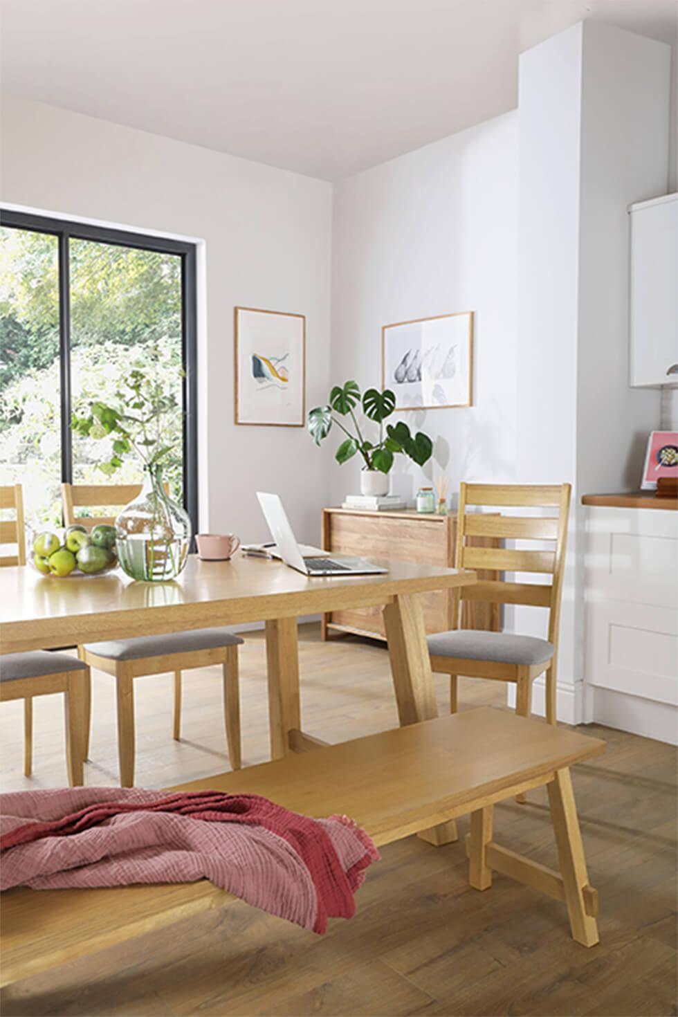 Working from home in an open plan kitchen with a wooden dining table and bench