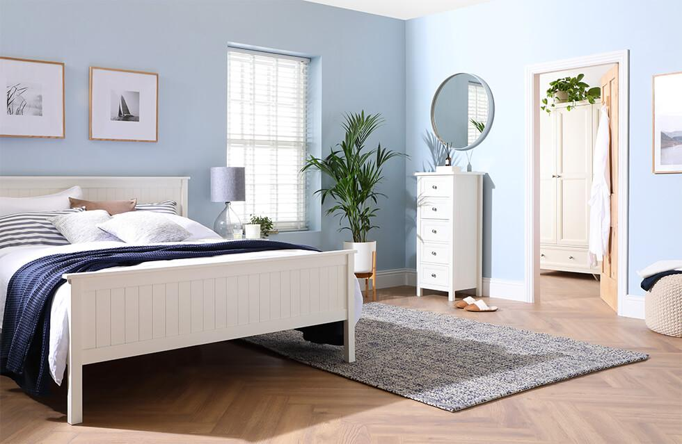 Relaxing blue bedroom with white wooden bed