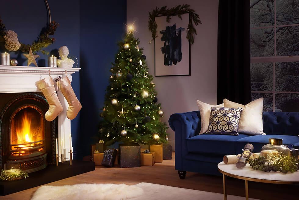 Blue living room with blue velvet Chesterfield sofas, white cushions and carpet, and Christmas tree