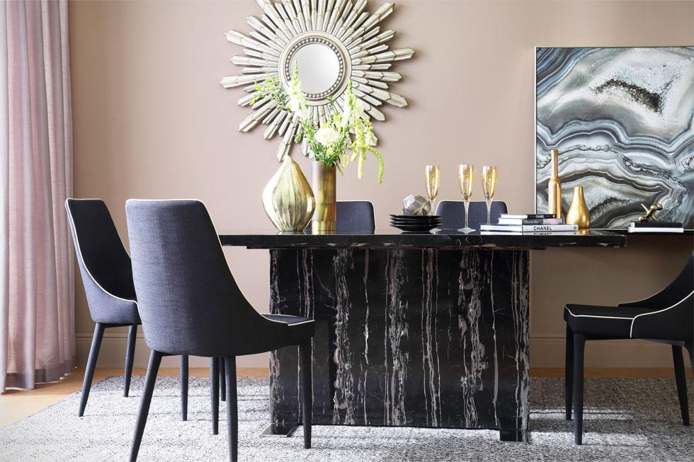 Marbled effect table with black dining chairs.