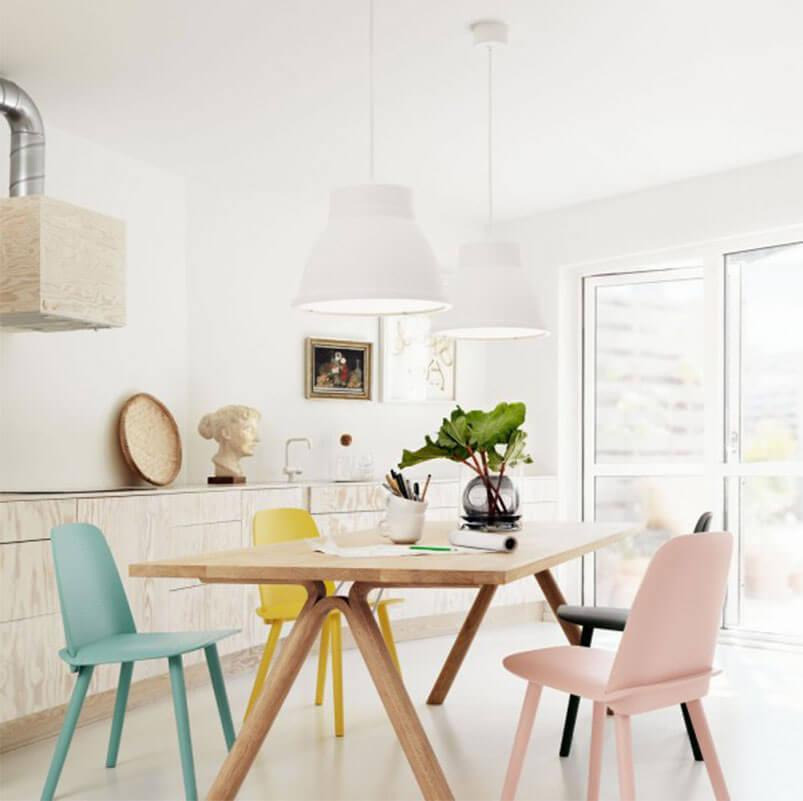 An airy dining room with pastel dining chairs.