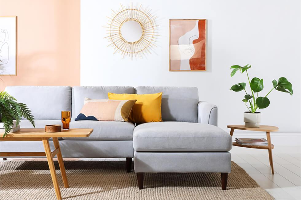 Colourful mid-century living room with grey fabric sofa, tables with tapered legs and sunburst decor