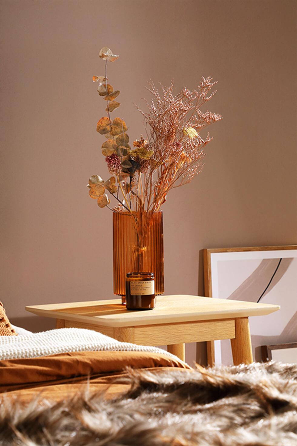 Warm toned room with wooden bedside table, brown glass jar with dried flowers and fur throw