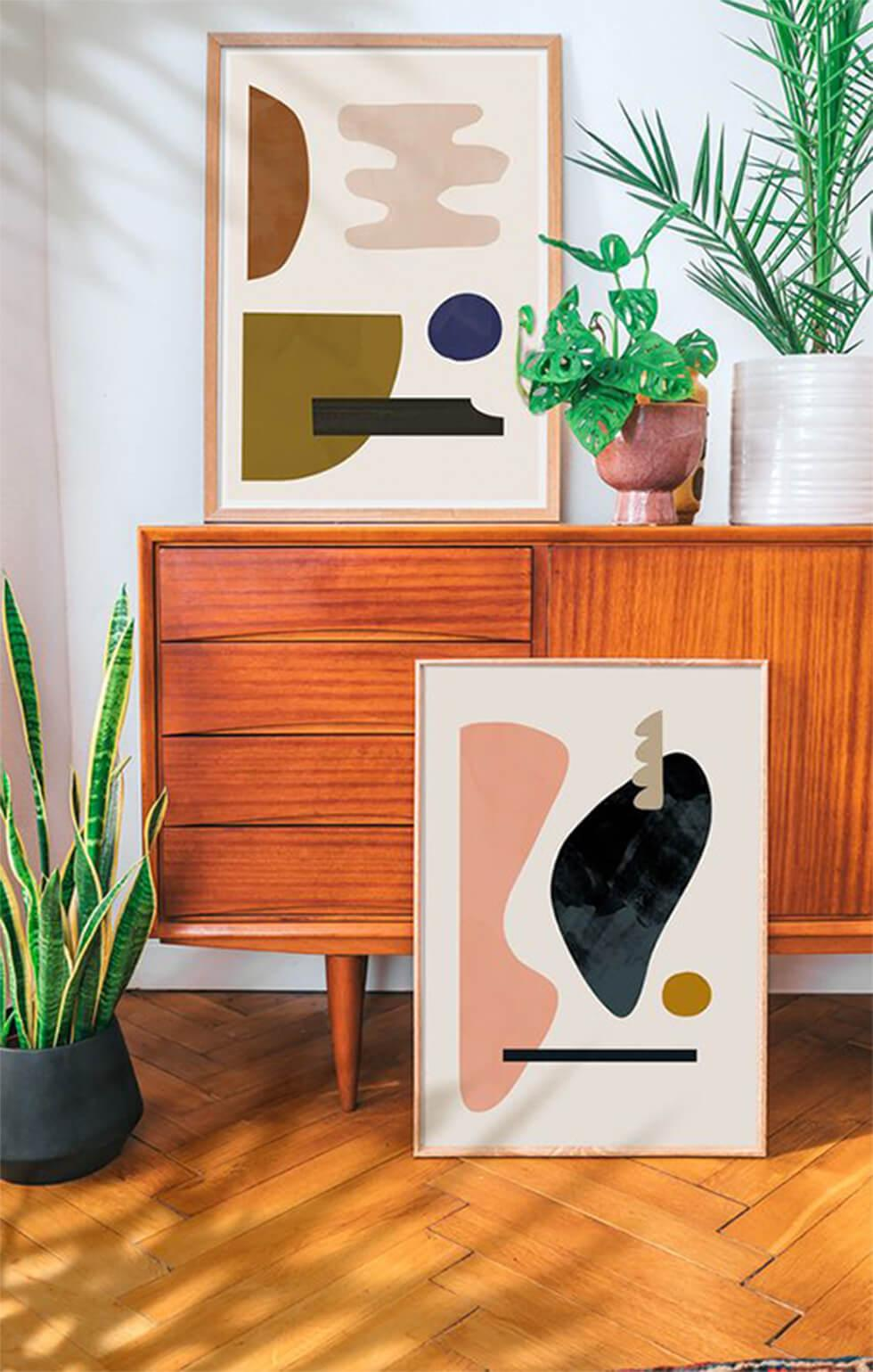 Framed mid-century art against a credenza with indoor plants