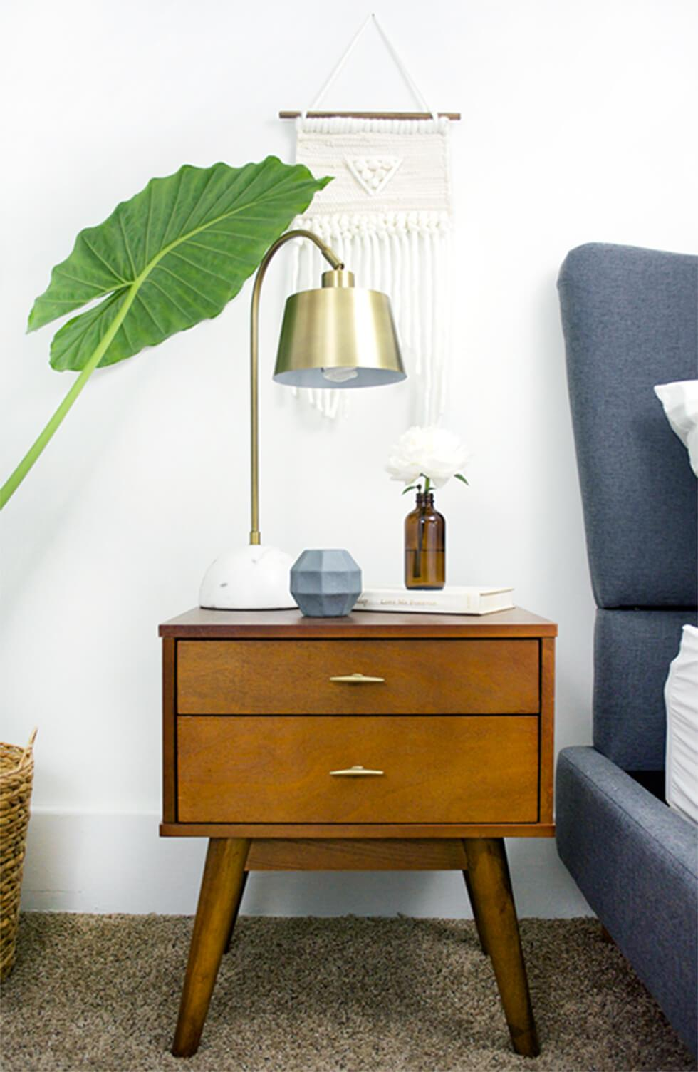 Bedside wooden chest of drawers with splayed legs and a brass lamp